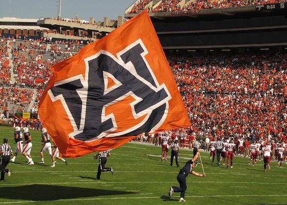 Auburn cheerleader waving Auburn Ffag